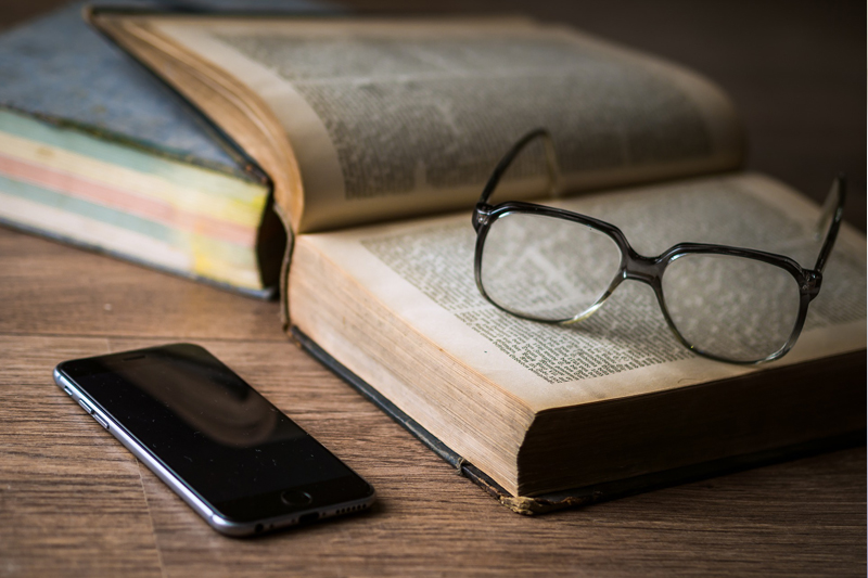 Glasses, books and a phone on a desk